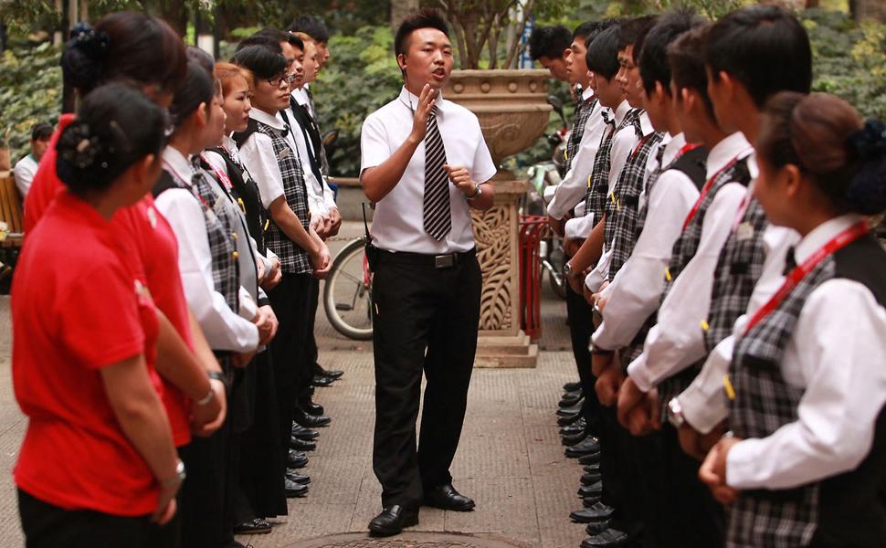 2012年9月26日,昆明,一餐厅的大堂经理为服务员做工作培训.图片